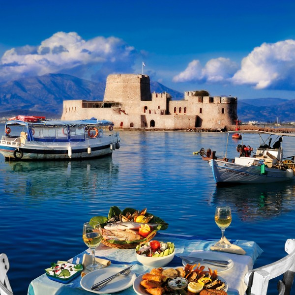 A table prepared for lunch & fishing boats in the bay in front of Bourtzi castle in Nafplio, Greece