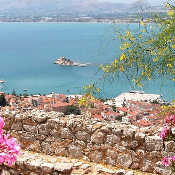 Flowers overlooking a town & bay on the Greek mainland, one of the sights on the ASIT 11 day tour.