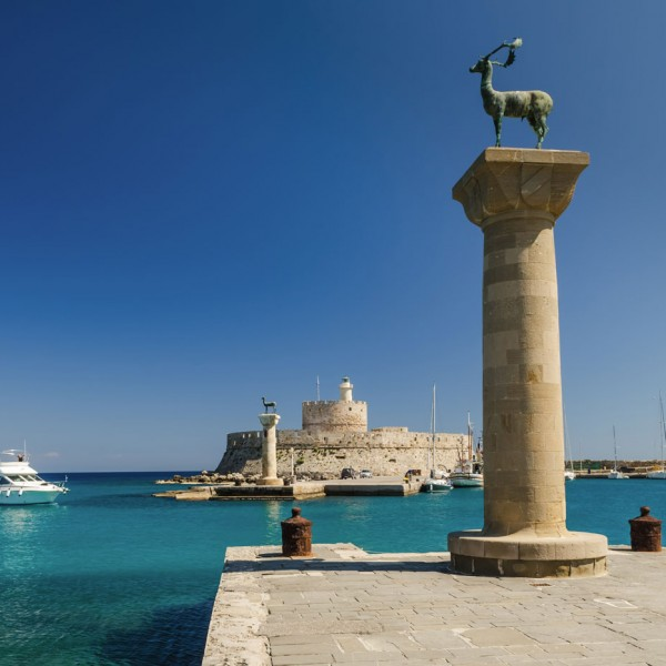 Pillars & boat at the entrance to the harbour at the Greek island of Rhodes on the ASIT 7 day cruise
