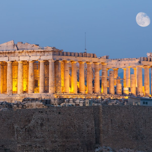 Athen's stunning ancient Parthenon illuminated at dusk, with the moon in the sky above it.