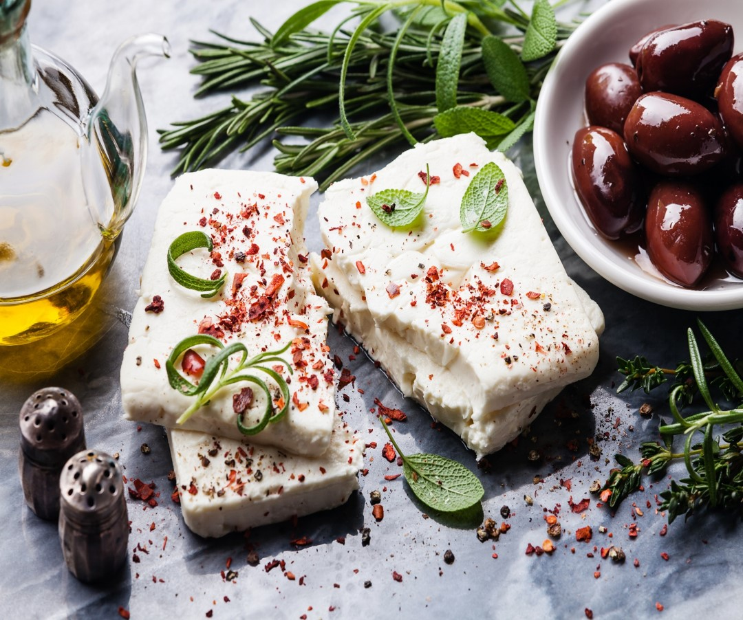 Feta cheese, olives, herbs, & olive oil on a table. ASIT's Thessaloniki tours include a Food Tour