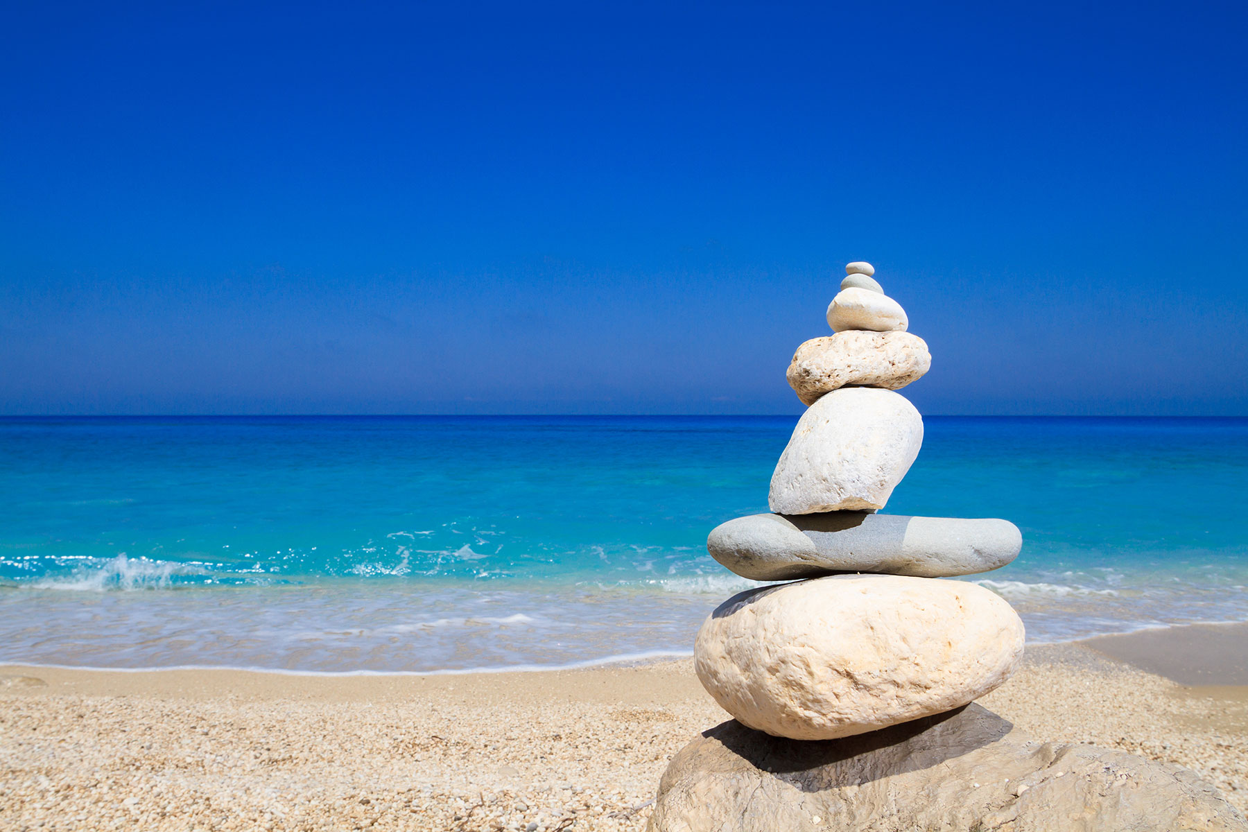 A pile of stones on a sandy beach in Greece looking out to the azure blue Mediterranean sea