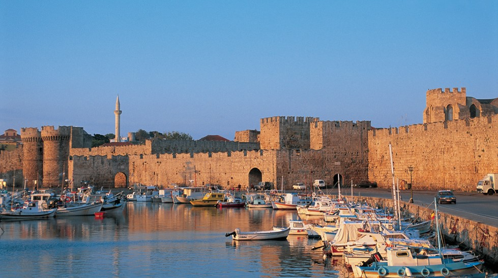 Fishing boats in the harbour in front of the medieval walls of Rhodes, a UNESCO World Heritage Site