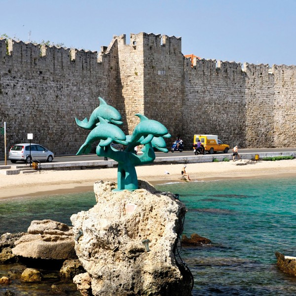 Dolphin sculpture on a rock by the Rhodes harbour walls, part of ASIT's island vacation from Athens