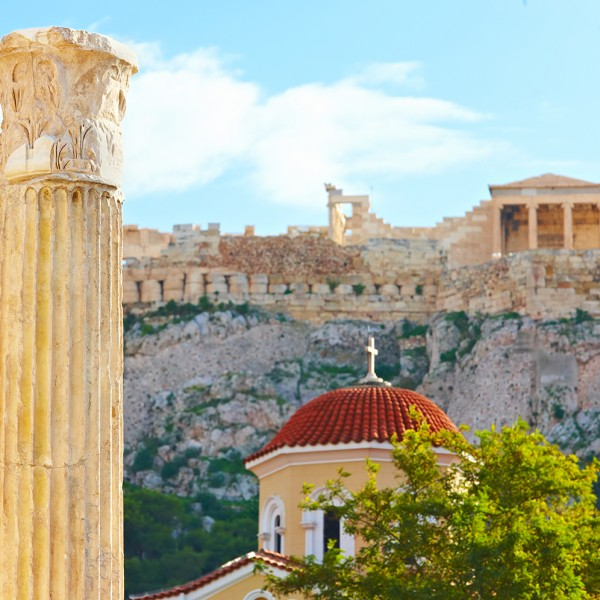 A column & domed church in front of the ancient Acropolis perched above the city of Athens