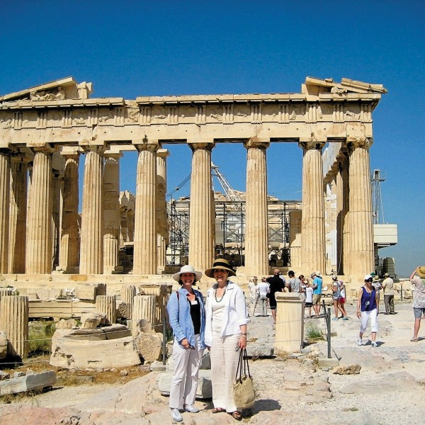 Visitors stand in front of Athens' ancient Parthenon on the ASIT 6 day classical Greece tour package