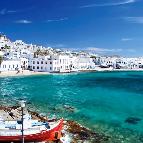 Fishing boats in a bay in front of whitewashed Mykonos town, an ASIT vacation package destination