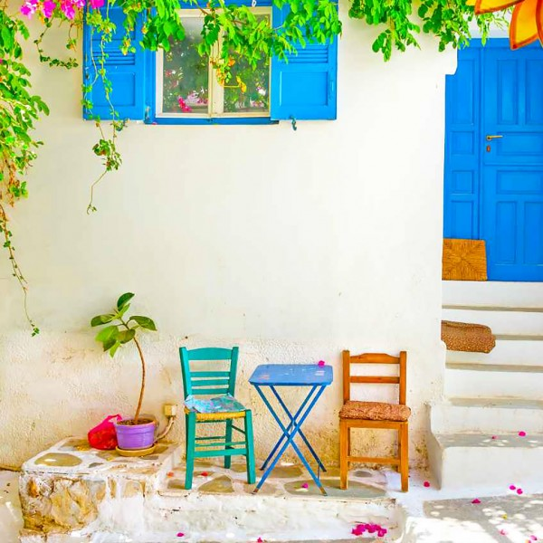 Traditional Greek island house in Mykonos with blue door & shutters, & chairs & table outside.