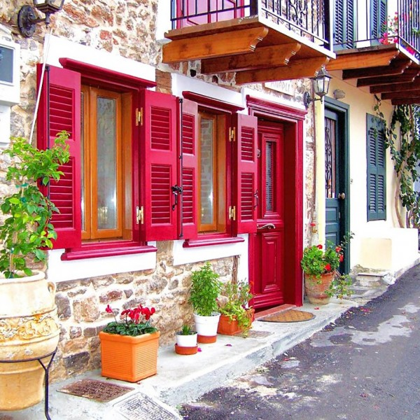 Traditional house with red door & shutters in Nafplion town in the Greek Peloponnese peninsular