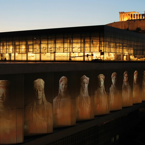 Athens' impressive modern design new Acropolis museum below the Parthenon at night.